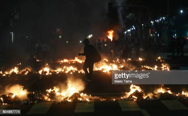 A man walks past street fires set during a demonstration against labor and pension reforms proposed by President Michel Temer during a nationwide...