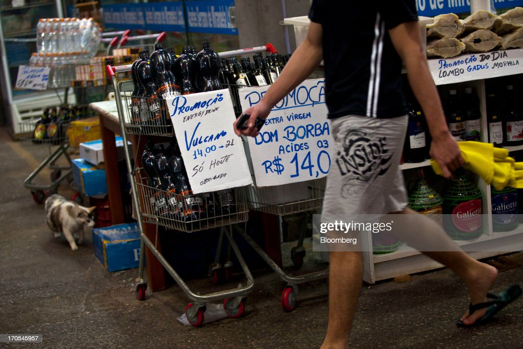 A man walks past supermarket carts offering olive oil and energy drinks for sale at a market in Rio de Janeiro, Brazil, on Thursday, June 13, 2013. Brazilian retail sales rose in April at less than half the pace economists forecast as inflation erodes purchasing power, complicating the governments effort to boost growth. Photographer: Dado Galdieri/Bloomberg via Getty Images