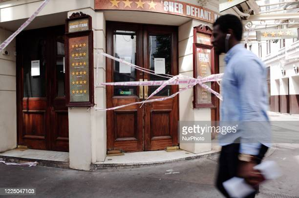 Man walks past tape bearing the message 'Live Theatre Missing' stretched across the entrance to the closed Ambassadors Theatre, previously showing...