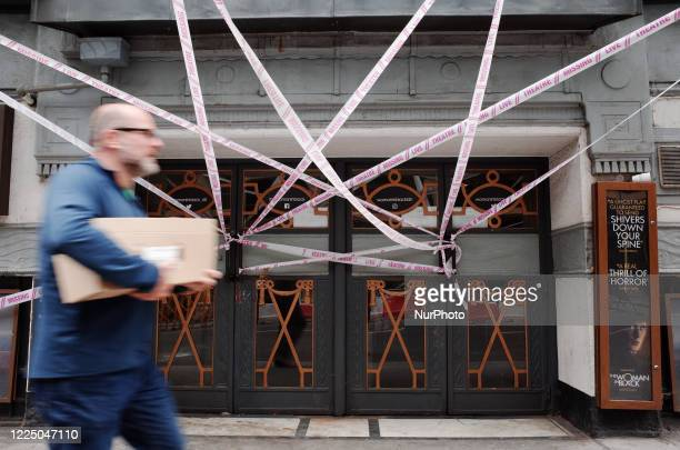Man walks past tape bearing the message 'Live Theatre Missing' stretched across the entrance to the closed Fortune Theatre, home to horror adaptation...