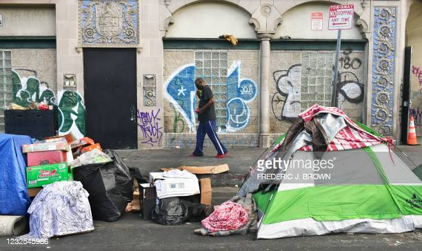 Man walks past tents housing the homeless on the streets in the Skid Row community of Los Angeles, California on April 26, 2021. - A federal judge...