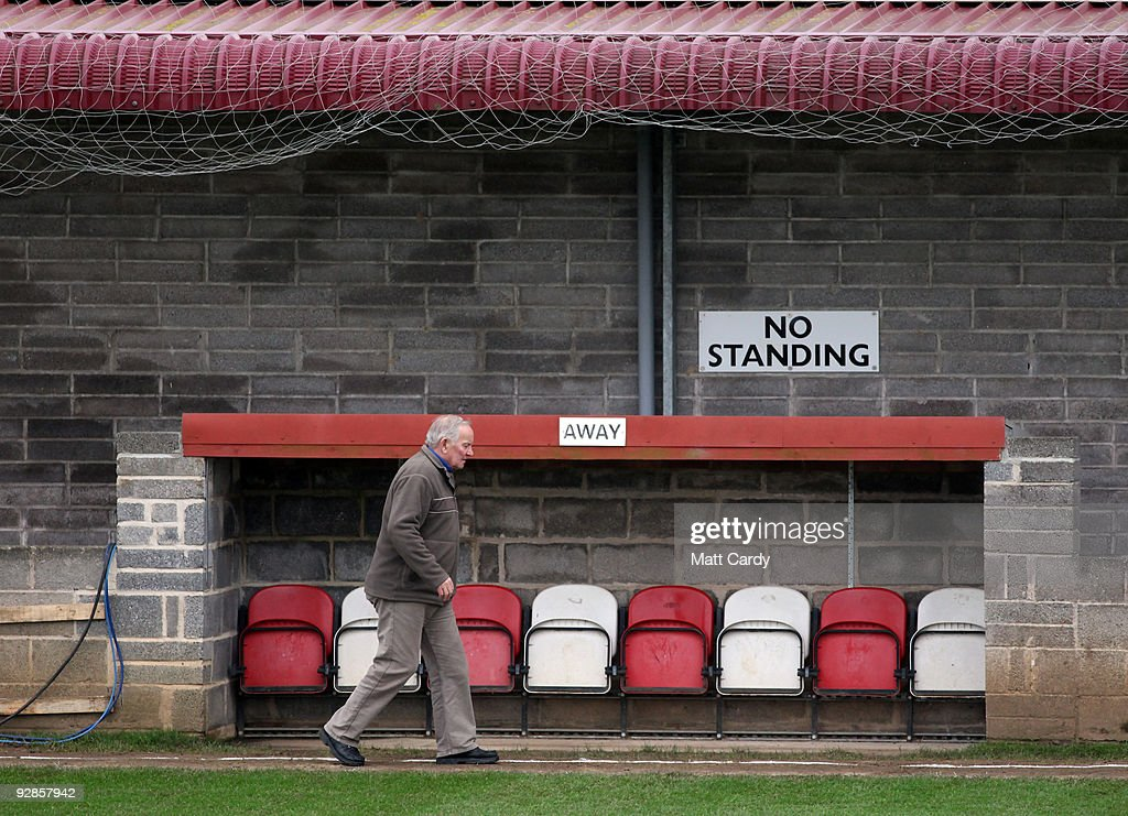 A man walks past the away team manager's dug-out at Paulton Rovers Football Club on November 6, 2009 in Paulton, England. Non-league Paulton Rovers are currently preparing for the single biggest day in their 128-year history as they face Norwich City in the FA Cup first round tomorrow. The Somerset village club, which beat Chippenham Town before being drawn against the League One club, normally has an attendance of 200, but will see capacity at the ground swell to 2500 and the match broadcasted live on television to an estimated audience of 2 million.