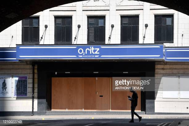 Man walks past the boarded-up Ritz nightclub in the near-deserted city centre of Manchester, north-west England on April 15 during the nationwide...