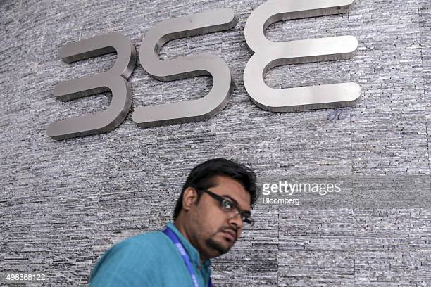 A man walks past the Bombay Stock Exchange logo displayed outside the building's lobby in Mumbai India on Monday Nov 9 2015 India's rupee fell the...