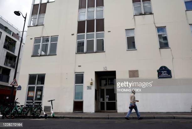 Man walks past the building where journalists of the Charlie Hebdo newspaper were killed by jihadist gunmen in January 2015, in Paris, on August 30,...