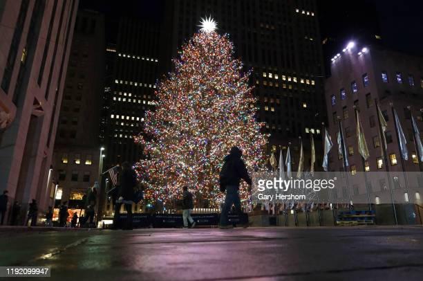 Man walks past the Christmas tree in Rockefeller Center before sunrise on December 5 in New York City.