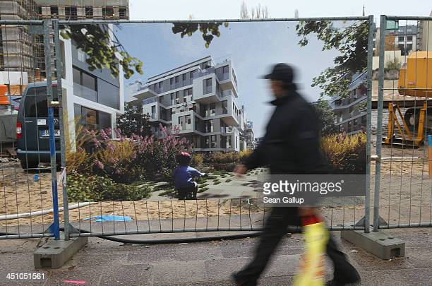 A man walks past the construction site of new residential apartments on November 20 2013 in Berlin Germany Low interest rates on loans and mortgages...