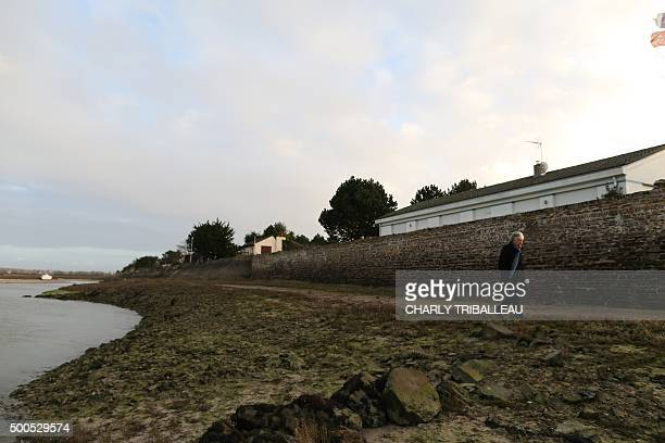 A man walks past the dam which protects hundreds of homes against high tides in BarnevilleCarteret northwestern France on December 8 2015 / AFP /...
