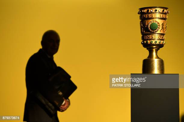 A man walks past the DFBPokal trophy of the German Cup football competition during the annual general meeting of German first division Bundesliga...
