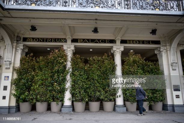 A man walks past the entrance of The Fairmont Le Montreux Palace hotel hidden by plants in Montreux on May 29 which is scheduled to host the annual...