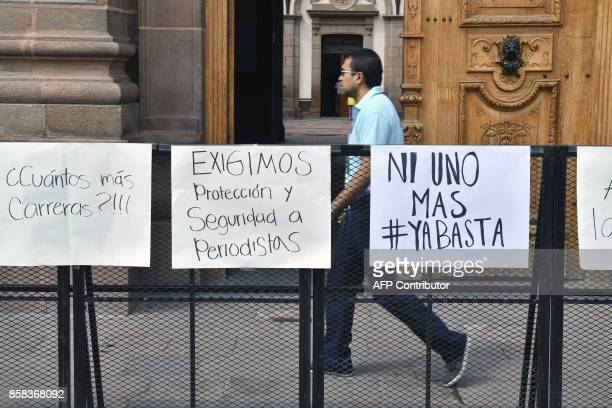 A man walks past the entrence of the government's palace during a demonstration to demand justice for slain Mexican photojournalist Edgar Daniel...