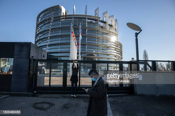 Man walks past the European Parliament building on February 21, 2021 in Strasbourg, eastern France. A year into the pandemic, the east of France...