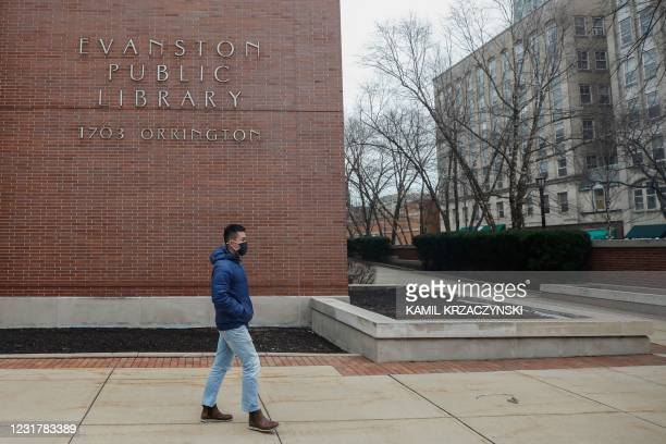 Man walks past the Evanston Public Library in Evanston, Illinois, on March 16, 2021. - A suburb in Chicago is set to become the first place in the...