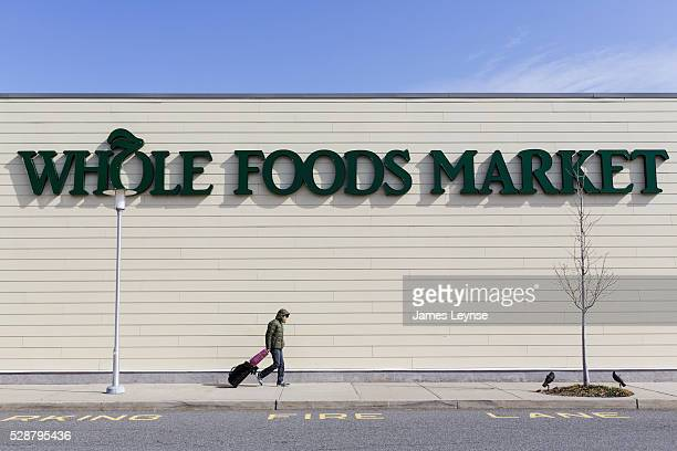 A man walks past the exterior of a Whole Foods Market in Paramus