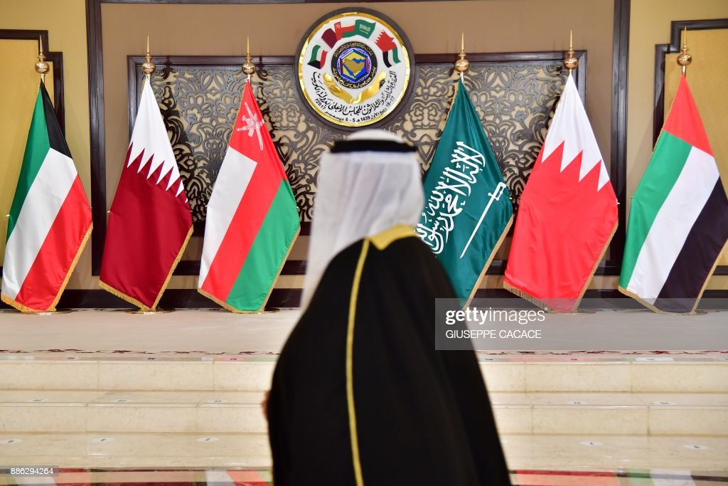 A man walks past the flags of the countries attending the Gulf Cooperation Council (GCC) summit at Bayan palace in Kuwait City on December 5, 2017. The Gulf Cooperation Council, which launches its annual summit today in Kuwait amid its deepest ever internal crisis, comprises six Arab monarchies who sit on a third of the world's oil. A political and economic union, the GCC comprises Saudi Arabia, the United Arab Emirates, Kuwait, Qatar, Oman and Bahrain. Dominated by Riyadh, it is a major regional counterweight to rival Iran. CACACE