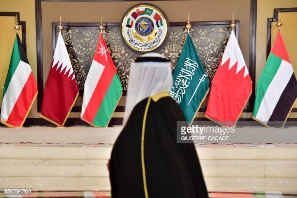 A man walks past the flags of the countries attending the Gulf Cooperation Council summit at Bayan palace in Kuwait City on December 5 2017 The Gulf...