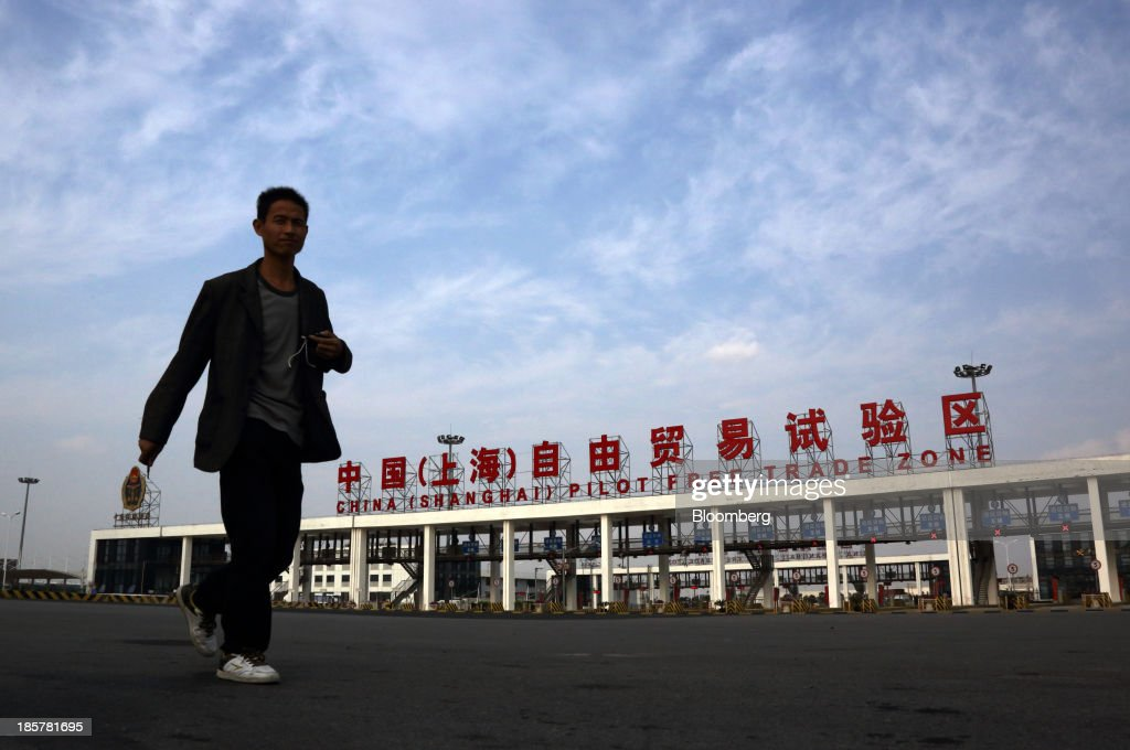 A man walks past the gate to China (Shanghai) Pilot Free Trade Zone's Pudong free trade zone in Shanghai, China, on Thursday, Oct. 24, 2013. The area is a testing ground for free-market policies that Premier Li Keqiang has signaled he may later implement more broadly in the world's second-largest economy. Photographer: Tomohiro Ohsumi/Bloomberg via Getty Images