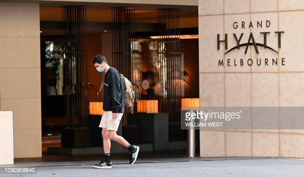 Man walks past the Grand Hyatt hotel in Melbourne on February 4 as preparations for the Australian Open were thrown into chaos when up to 600 players...