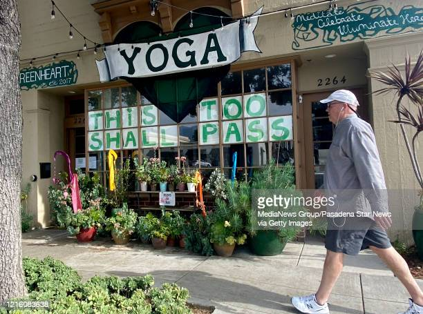 Man walks past the Greenheart Yoga Meditation Center with a sign in the window reading This Too Shall Past along Huntington Drive in San Marino on...