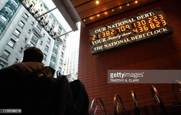 A man walks past the he National Debt Clock on 43rd Street in midtown New York City February 15 2019 The National Debt Clock is a billboard...