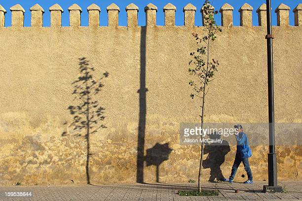 Man walks past the high, ancient ramparts in Fez. There are interesting shadows on the wall and the blue sky matches the man's jacket and compliments...