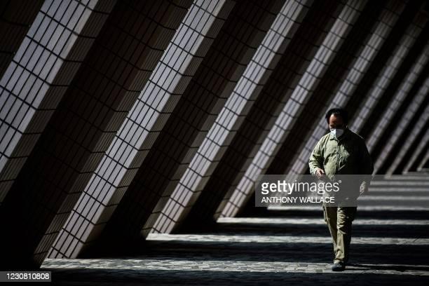 Man walks past the Hong Kong Cultural Centre in Hong Kong on January 27, 2021.