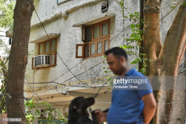 Man walks past the house where an elderly couple along with their domestic help were found murdered, at Vasant Apartments, in Vasant Vihar on June...