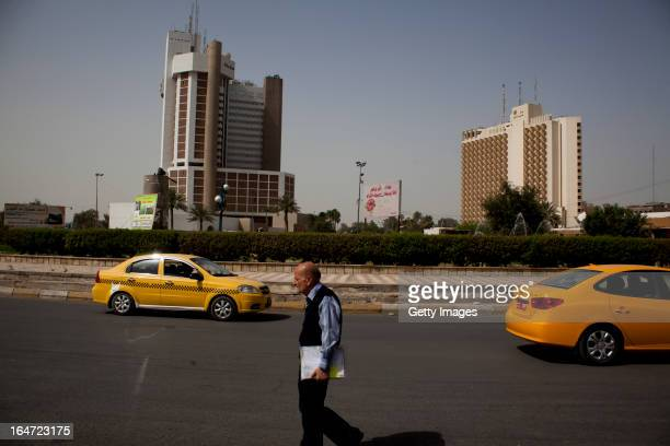 A man walks past the Ishtar and Palestine Hotels at Firdos Square March 18 2013 in Baghdad Iraq Ten years after the regime of Saddam Hussein was...