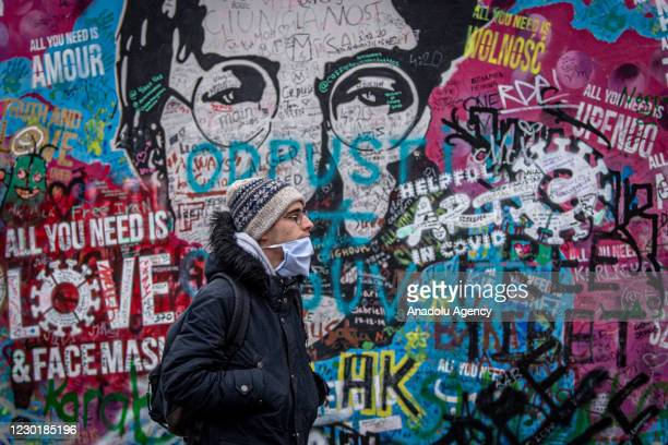 Man walks past the Lennon wall, a memorial wall dedicated to former Beatles musician John Lennon in Prague, Czech Republic on December 17, 2020. From...