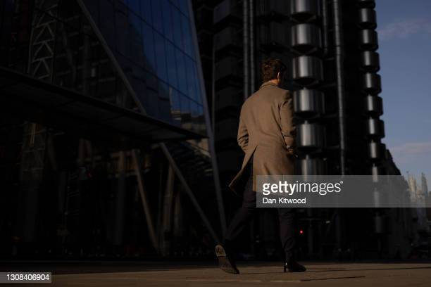 Man walks past the Lloyds of London building in the square mile on March 22, 2021 in London, England. A year since the British government issued its...
