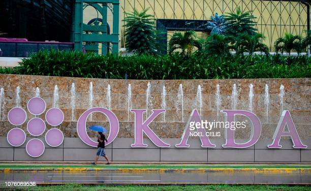 Man walks past the logo of Okada Manila in Manila on December 31, 2018. - A luxury Philippine hotel and casino has called off a world record attempt...