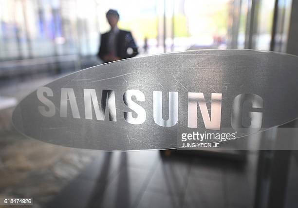 A man walks past the logo of Samsung Electronics at a flagship store in Seoul on October 27 2016 Samsung Electronics on October 27 reported an...