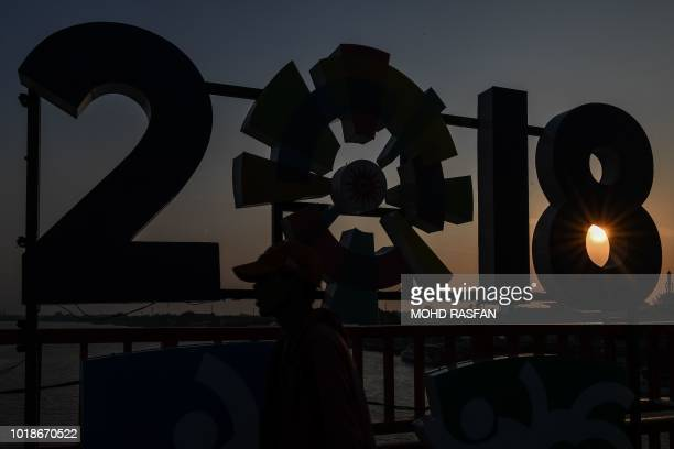 TOPSHOT A man walks past the logo of the 2018 Asian Games on Ampera bridge on the eve of the opening ceremony in Palembang on August 18 2018