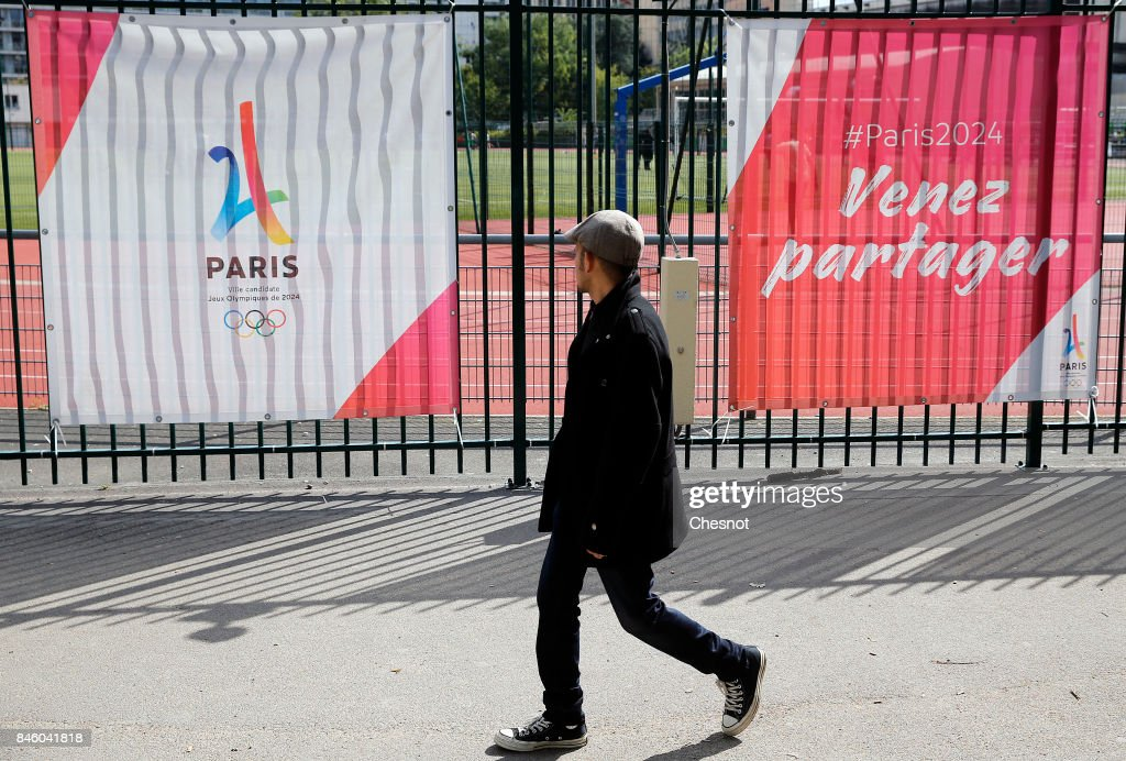 A man walks past the logo of the Paris candidacy for the 2024 Olympic Games next to the Eiffel tower on September 12, 2017 in Paris, France. For the first time in history, International Olympic Committee (IOC) confirms two summer Games host cities at the same time, Paris will host the Olympic Games in 2024 and Los Angeles in 2028. The official announcement by the IOC will take place tomorrow 23 September in Lima, Peru.