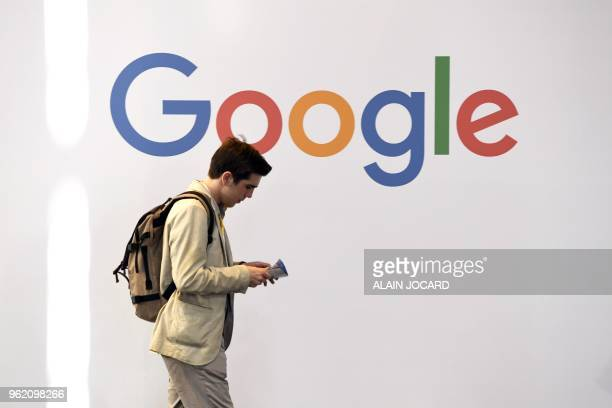 A man walks past the logo of the US multinational technology company Google during the VivaTech trade fair on May 24 2018 in Paris