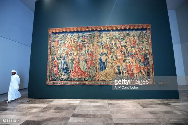 TOPSHOT A man walks past the medieval 'Tapestry of Daniel and Nebuchadnezzar' displayed at the Louvre Abu Dhabi Museum during a media tour on...