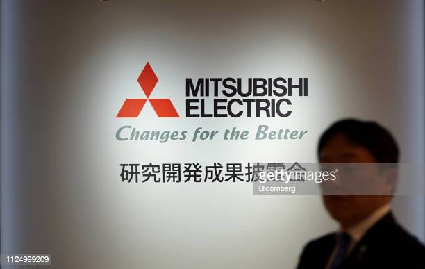 Man walks past the Mitsubishi Electric Corp. Logo displayed during a media event in Tokyo, Japan, on Wednesday, Feb. 13, 2019. Mitsubishi Electric...
