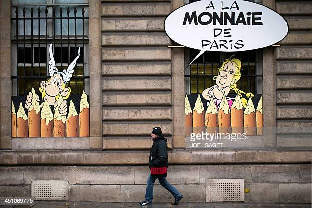 A man walks past the Monnaie de Paris building on November 21 as card board decorations representing comic characters of 'Asterix and Obelix' are...