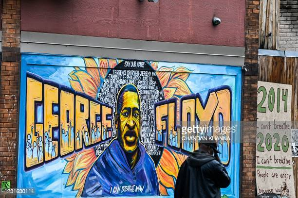Man walks past the mural of George Floyd near the makeshift memorial of George Floyd before the third day of jury selection begins in the trial of...