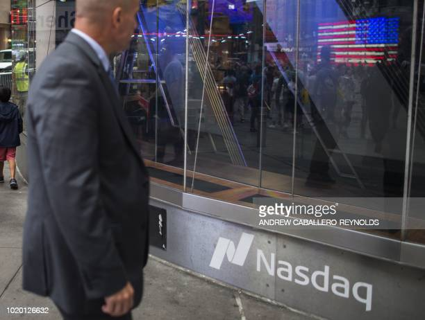 A man walks past the Nasdaq building in Times Square in New York on August 20 2018 Wall Street stocks were mostly higher early Monday on hopes that...