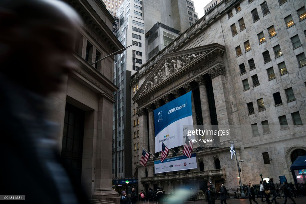 A man walks past the New York Stock Exchange (NYSE), January 12, 2018 in New York City. The Dow was up over 200 points on Friday, off to its best start to begin a year since 2003.