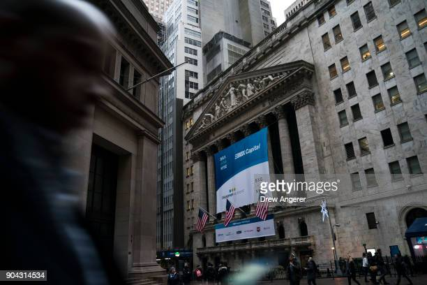 A man walks past the New York Stock Exchange January 12 2018 in New York City The Dow was up over 200 points on Friday off to its best start to begin...