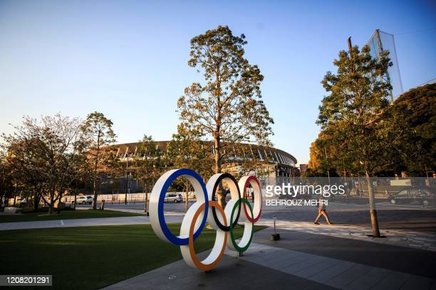 A man walks past the Olympic rings in front of the Japan National Stadium the main venue for the Tokyo 2020 Olympic Games in Tokyo on March 25 the...