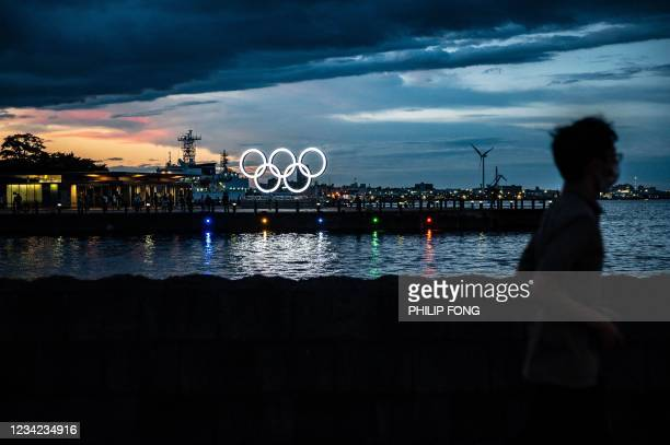 Man walks past the Olympic Rings lit up at dusk in Yokohama on July 27, 2021.