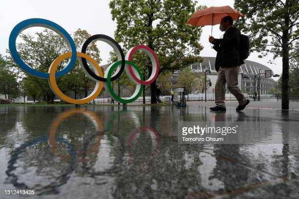 Man walks past the Olympic Rings near the National Stadium, the main stadium for the Tokyo Olympic and Paralympic Games, on the day marking 100 days...
