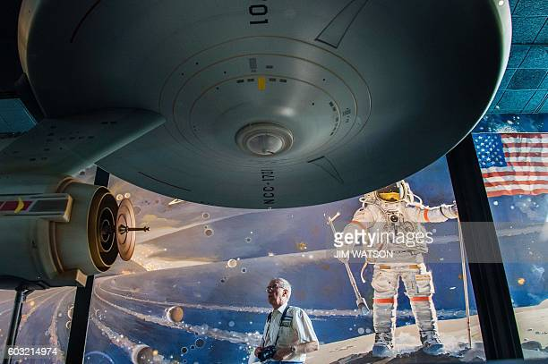 A man walks past the original model of the starship USS Enterprise from the television series Star Trek as it hangs on display at the Smithsonian Air...