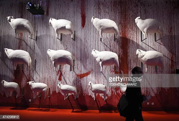 """Man walks past the piece named """"Sheep"""" by Korean artist Kyu Seok Oh at the exhibition Obedience: An Art Installation in 15 Rooms by multimedia artist..."""