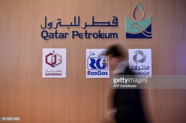 A man walks past the Qatar petroleum stand on July 11 2017 during 22nd World Petroleum Congress in Istanbul Oil major bosses and energy ministers are...