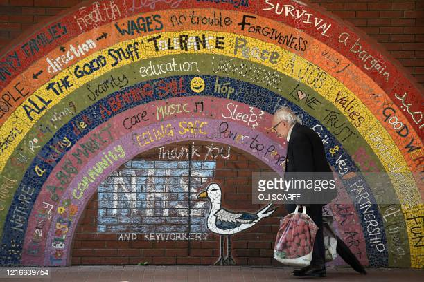 Man walks past the Rainbow of Hope mosaic installation created by local social enterprise Seagulls Reuse as stalls open for business in the outdoor...