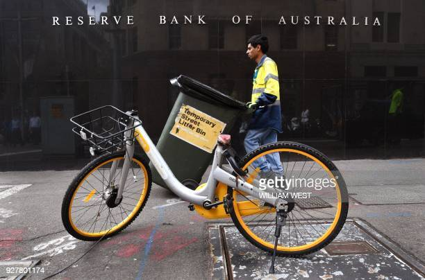 A man walks past the Reserve Bank of Australia building in Sydney on March 6 as Australia's central bank kept interest rates at a record in a widely...